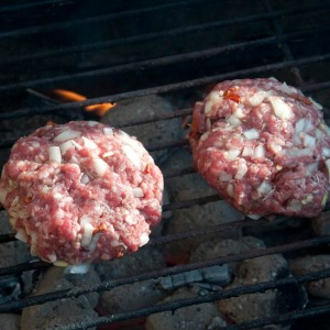 Burgers cooking over charcoal