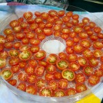 Arrange halved tomatoes on trays