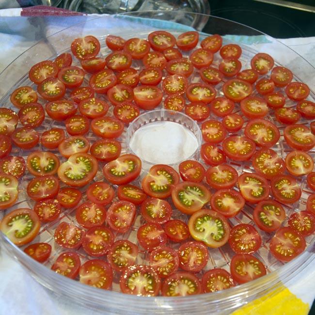 Arrange halved tomatoes on trays
